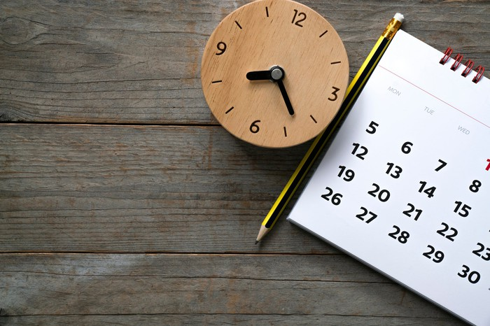 A brown clock next to a pencil and a calendar on top of a table.