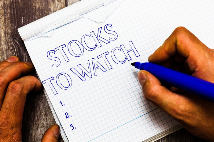 A person writing stocks to watch on a pad of paper.
