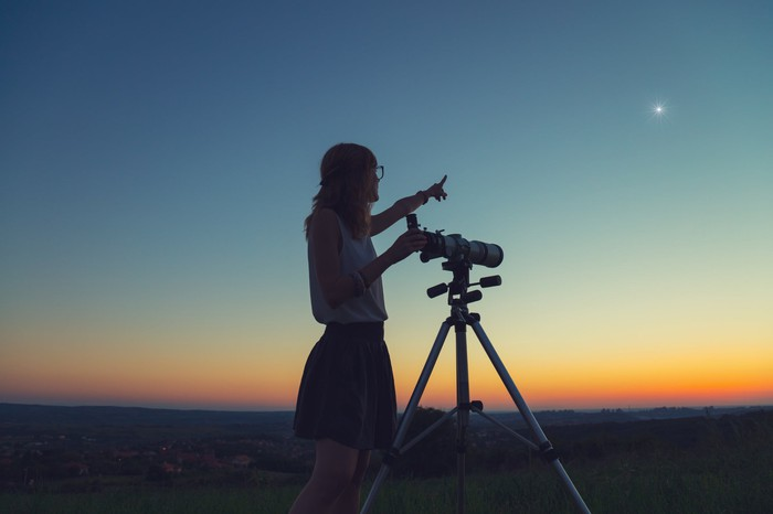 A woman stands next to a telescope at dusk and points to a bright star int he evening sky.