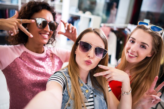 Three female shoppers try on sunglasses.