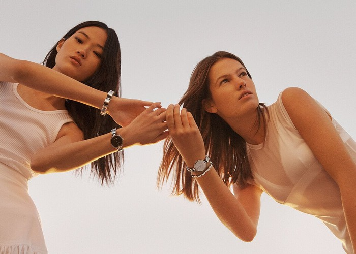 Two women modeling Calvin Klein watches and apparel.