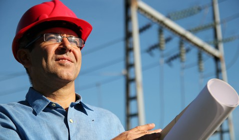 18_09_20 A man with blueprints and high voltage power lines behind him_GettyImages-525436881