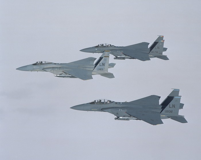 Three Boeing F-15s fly above the clouds.