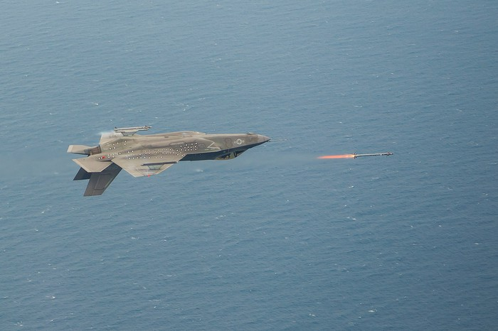 A Lockheed Martin F-35 flying inverted and firing a missile.