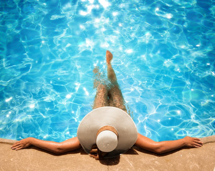 A woman in a sun hat lounges at the edge of a pool