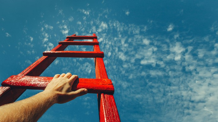 A red ladder going up towards a blue sky