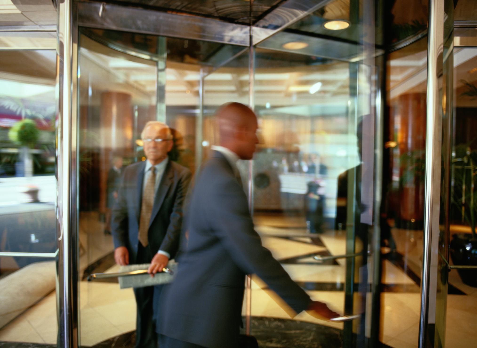 Two businessmen in a revolving door.