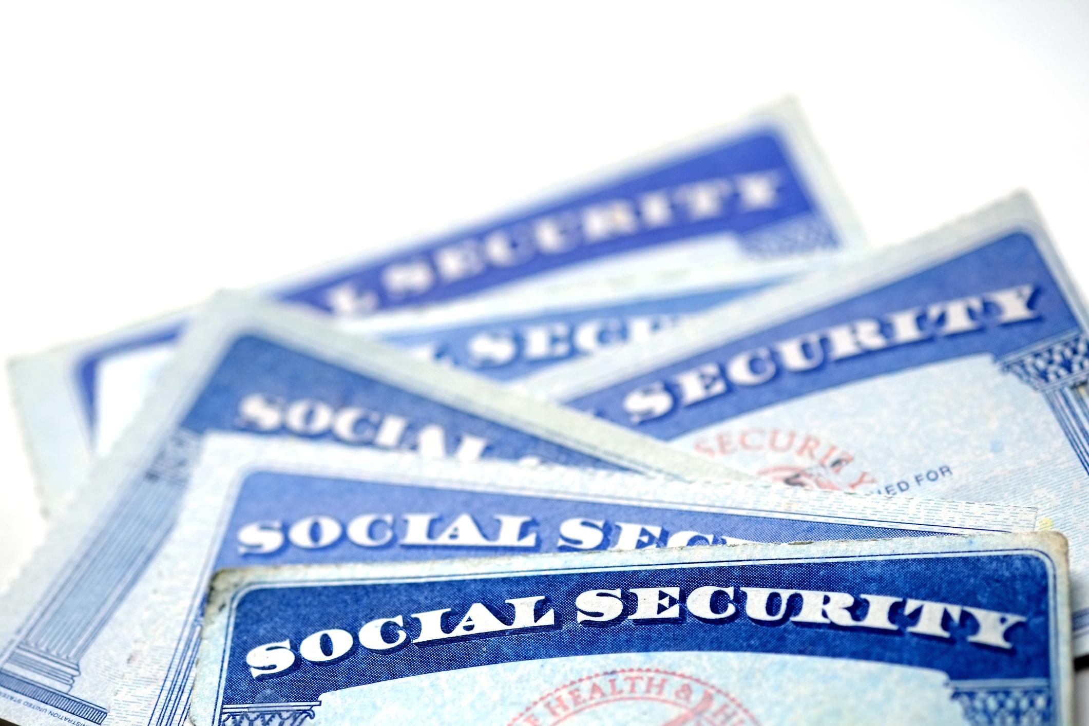 A half-dozen Social Security cards messily laid on a counter.