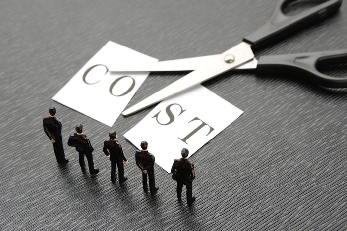 Scissors cutting a paper with the word Cost printed on it, as tiny model businesspeople look on