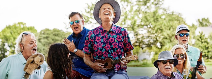 Bill Murray plays a ukelele surrounded by four of his brothers and two women on a golf course.