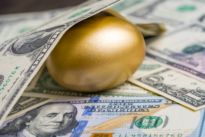 A gold egg surrounded by money.