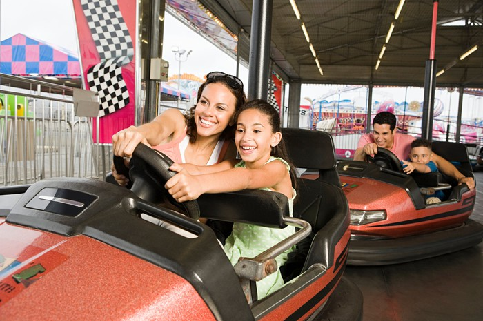A family on a bumper cars ride at a theme park.