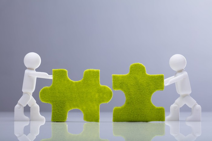 Two small white figurines pushing green jigsaw puzzle pieces together