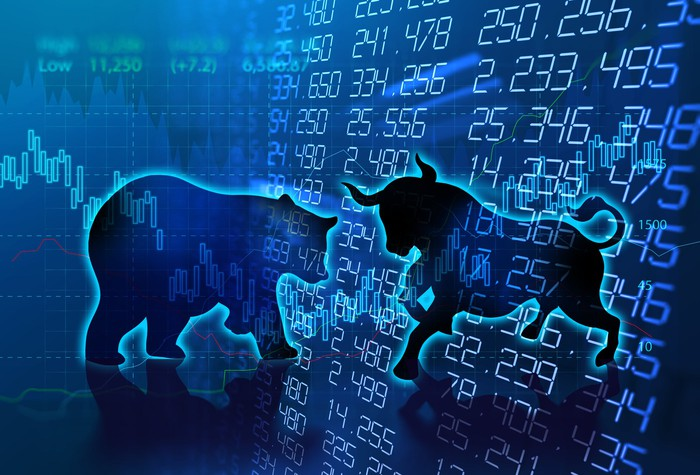 Silhouettes of a bull and bear on top of a stock market chart.