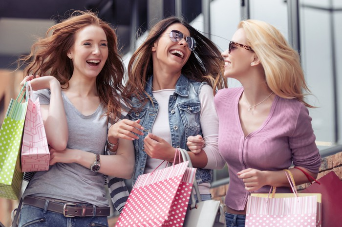 Women laughing and holding shopping bags.