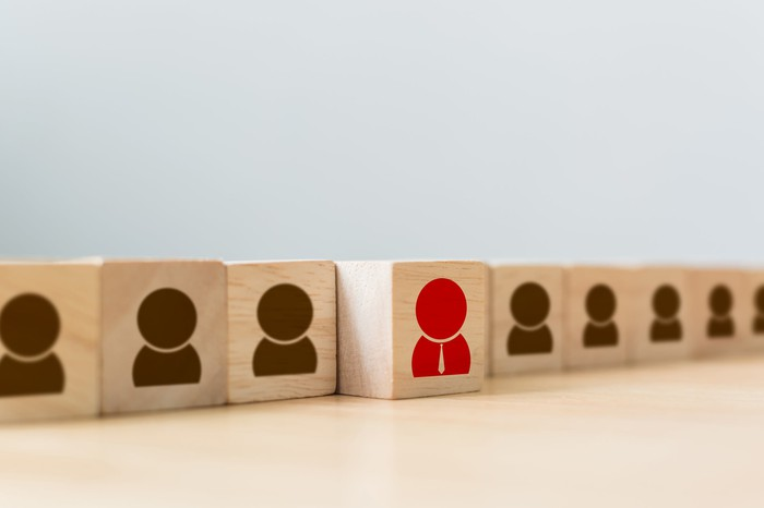 Building blocks stamped with brown human figures and a single red figure to represent a hiring process.