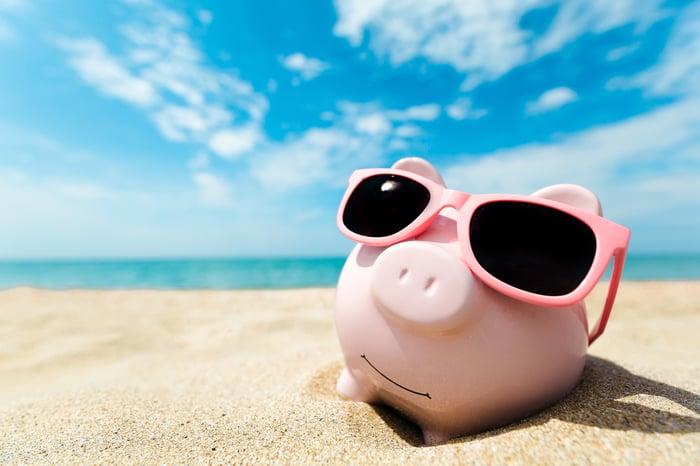 A piggy bank wearing pink sunglasses on a beach