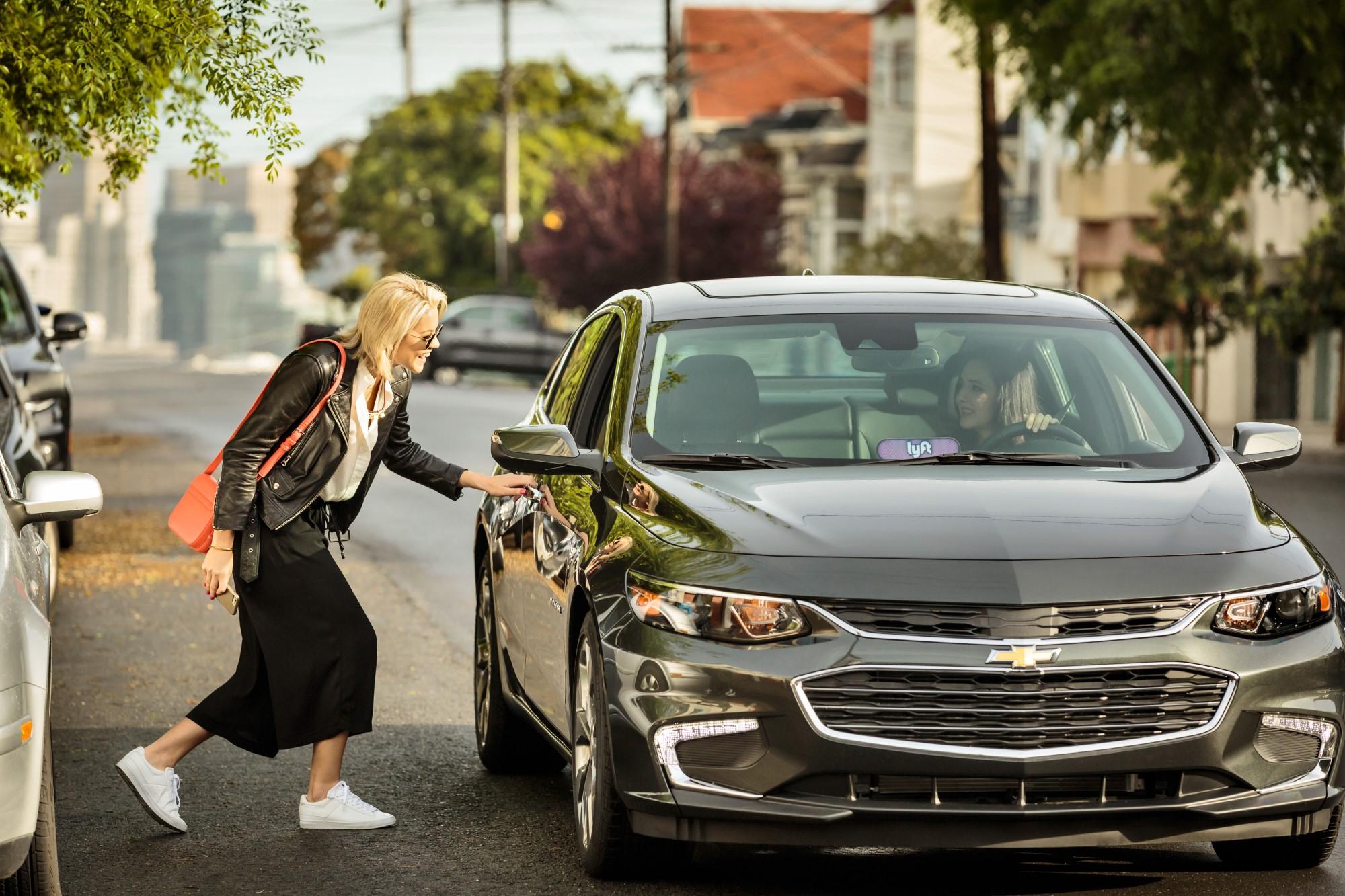 A woman entering a sedan bearing the Lyft Amp on the dashboard