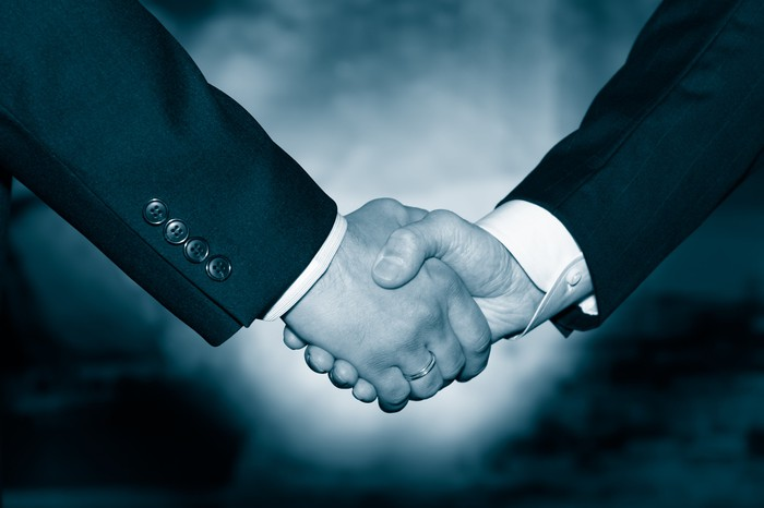 Two businessmen in suits shaking hands, as if in agreement