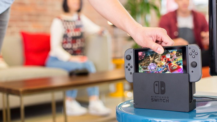 A hand placing a Nintendo Switch into its dock.
