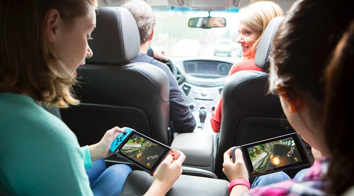 Two girls play games on their Switch consoles in the back of a car.