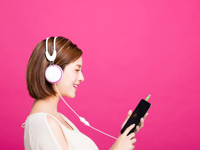 A young woman, set against a magenta background, listening to music through white headphones attached to her black smartphone.