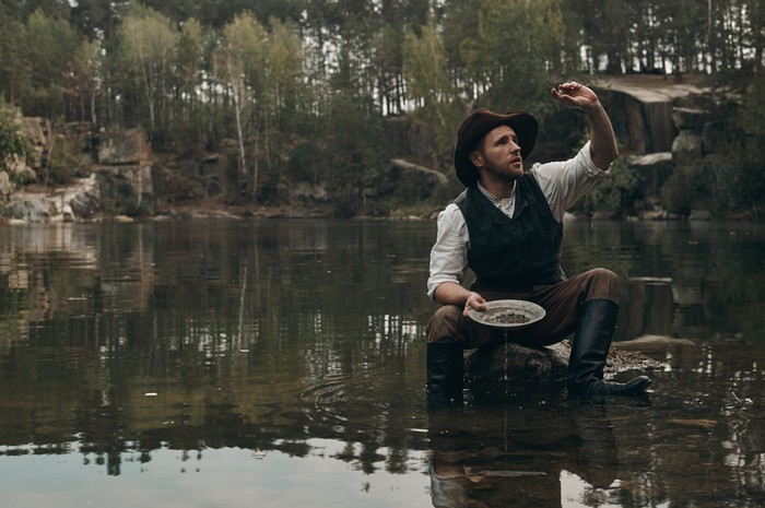 A man panning for gold, holding up a rock in his hands