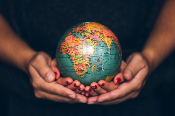 A man and a woman with nested cupped hands holding a globe