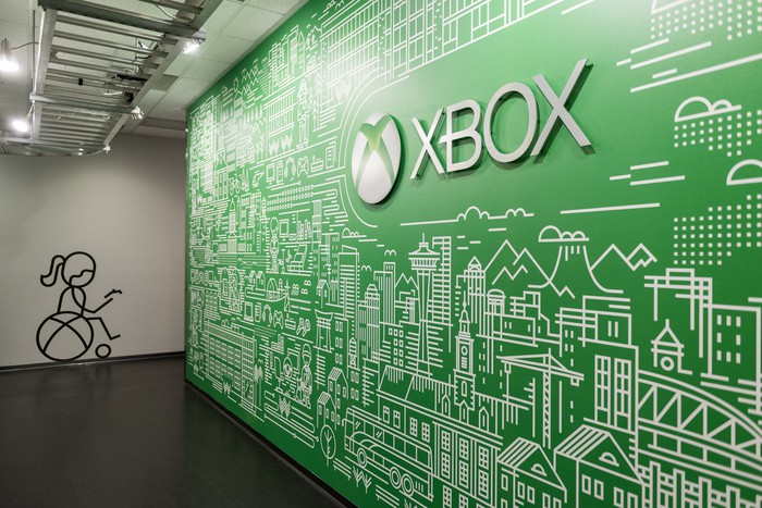 """A wall with the Xbox logo and the word """"XBOX"""" on it."""