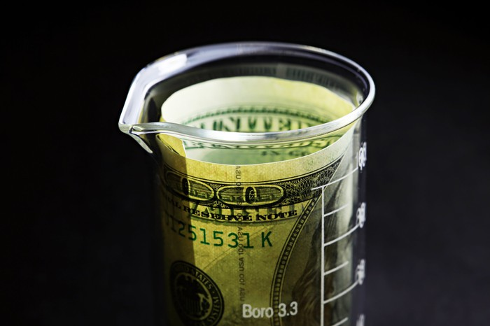 A lab beaker with a hundred dollar bill curled inside it.
