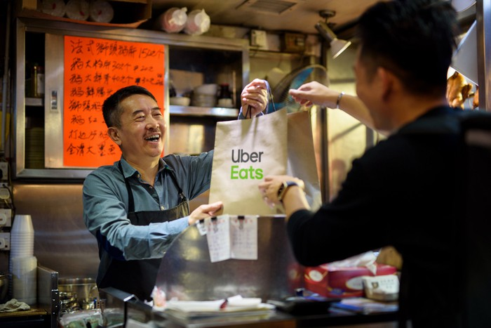 "Man handing an ""Uber Eats"" bag to another man."