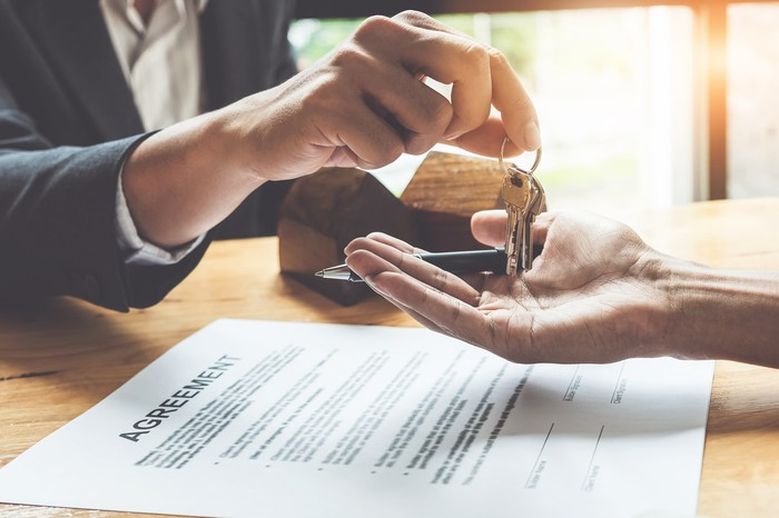 A person hands a set of keys across a desk to a person signing an agreement.