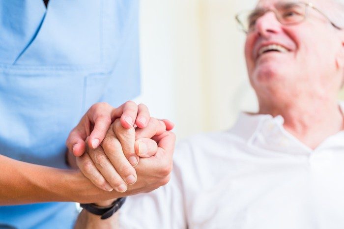 A senior holding a health aide's hand.