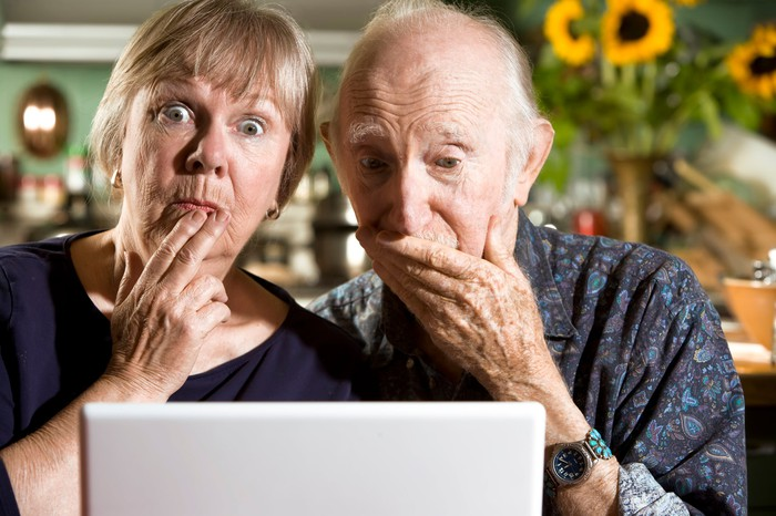 A retired couple looks surprised by what they're reading on a computer monitor.