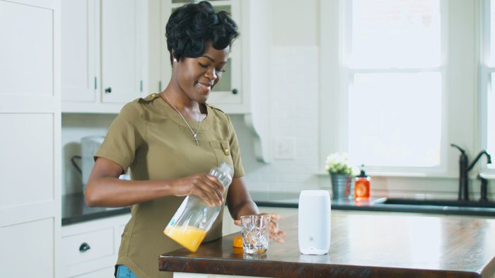 A woman pouring orange juice into a glass that's on a kitchen island with a Google Home speaker on it.