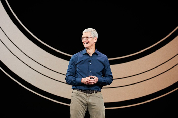 Apple CEO Tim Cook smiling and standing on a stage.