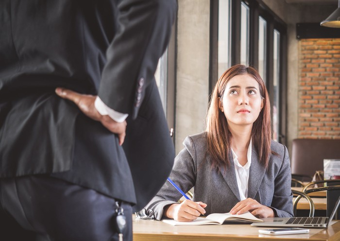 Woman in business suit seated at desk with annoyed expression looks up at man in suit who has his hands on his hips.