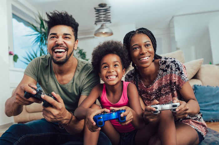 A man, woman, and child with video game controllers in their hand, sitting on a couch and smiling.