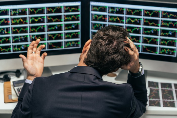 A visibly frustrated businessman in a suit grasping his head as he looks at two computer screens full of stock charts.