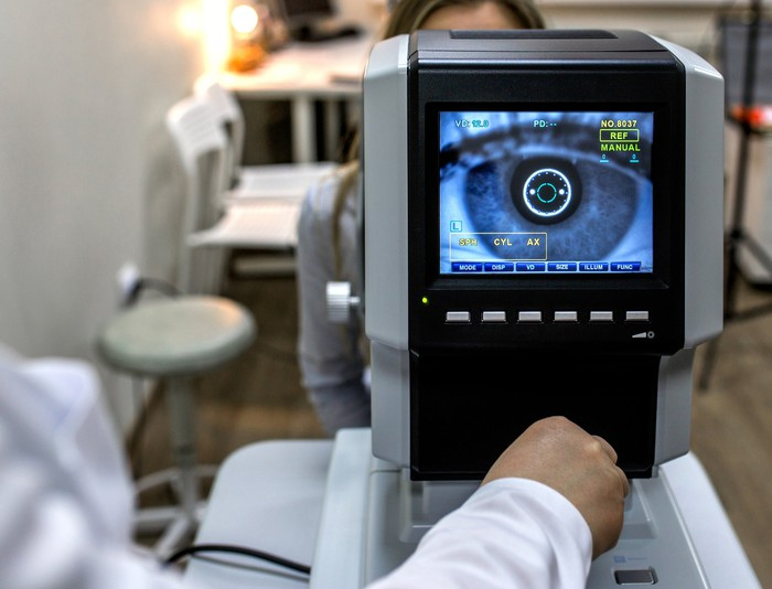 Image of woman's eye on a screen facing a person, presumably a healthcare professional who is examining the woman's eyes/vision.