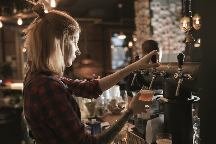 Woman bartender pouring beer from tap