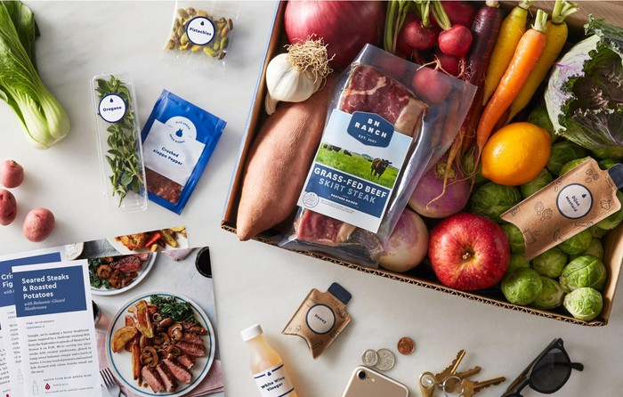 Blue Apron meal kit, containing ingredients like beef, carrots, onions, Brussels sprouts, and potatoes
