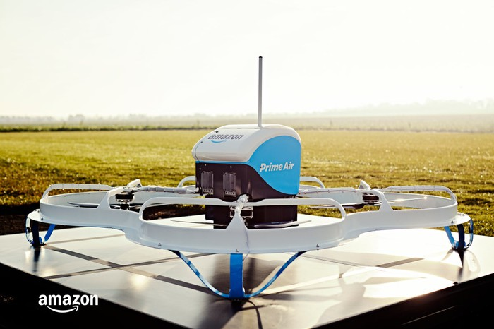An Amazon drone sits in the middle of a field.