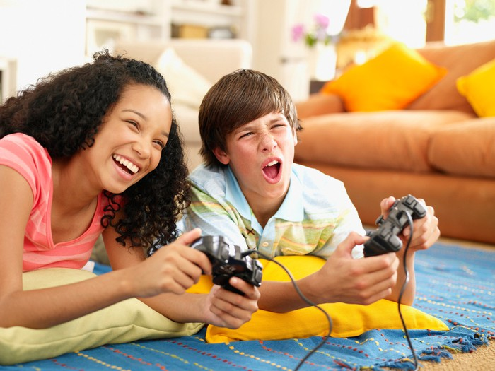 A young boy and girl lying on the floor, playing video games.