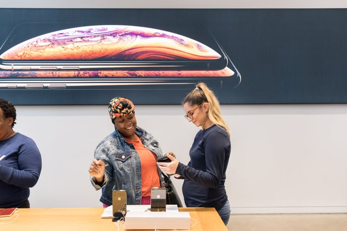 An Apple employee demonstrating the iPhone Xs to a customer in store.