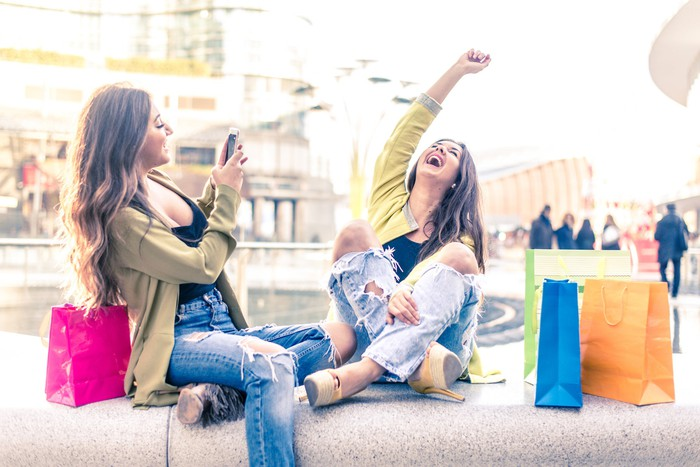 Two teen girls sitting with shopping bags and laughing while one is taking pictures of the other.