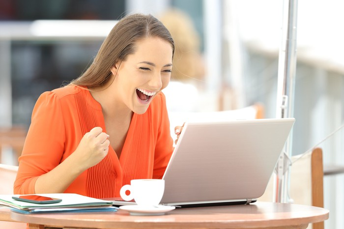 Woman holding up fist in celebration and smiling at laptop.