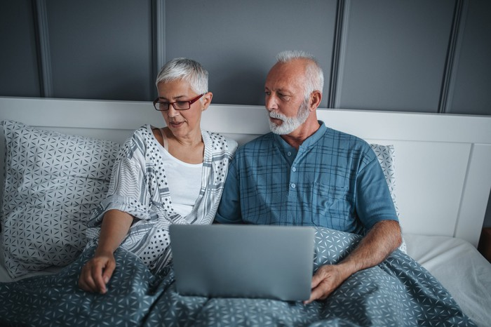An older man and woman sitting up in bed, with the man holding an open laptop.