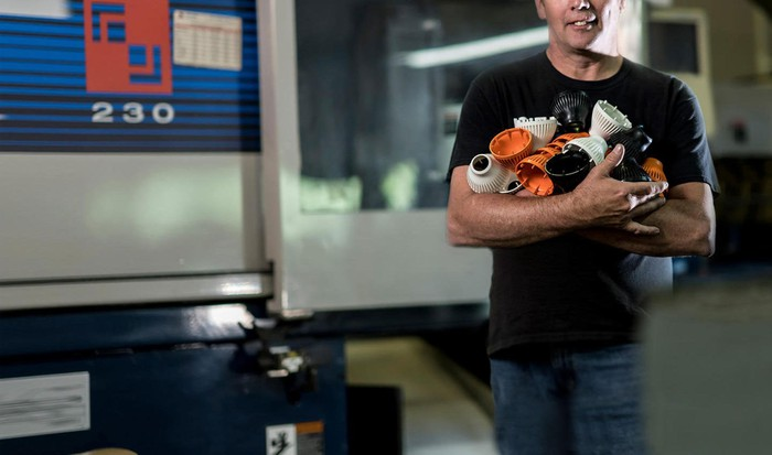 A man holding parts made by 3D Systems' Prox Dmp 300 3D printer.