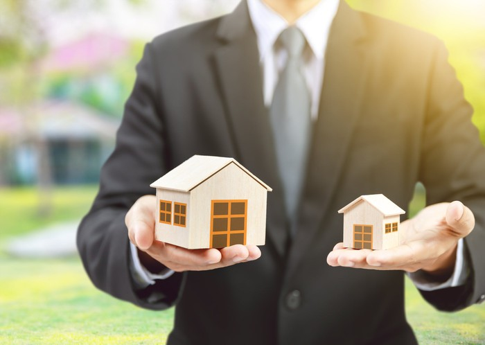 A person in a suit holding a big toy house in one hand and a small toy house in the other.
